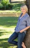 Femme se penchant sur le tronc d'arbre en parc Photos stock