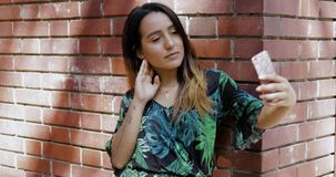 Femme se penchant sur un mur de briques utilisant un mobile banque de vidéos