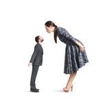 Femme se pliant en avant et embrassant le petit homme Photographie stock