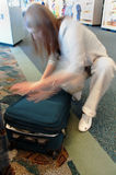 Femme se précipitant pour fermer la fermeture éclair le bagage à l'aéroport Photographie stock libre de droits