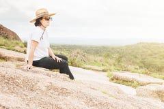 Femme se reposant heureusement sur un outcropping de roche Images stock