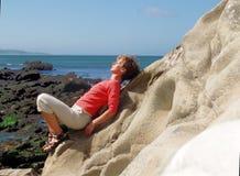 Femme se reposant par la mer Photographie stock libre de droits