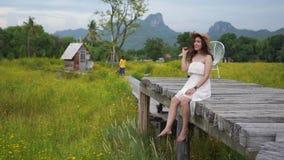 Femme se reposant sur le pont en bois avec le champ dans Lopburi, Tha?lande banque de vidéos