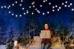 Femme se reposant sur une oscillation avec une couverture sous les lampes-torches Photo libre de droits