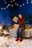 Femme se reposant sur une oscillation avec une couverture sous les lampes-torches Image stock