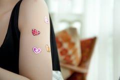 Femme se sentant heureusement dans l'amour avec des autocollants de coeur sur ses bras Images stock