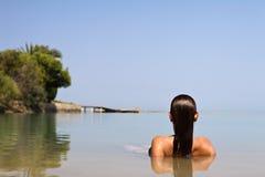 Femme se situant dans l'eau Photographie stock libre de droits