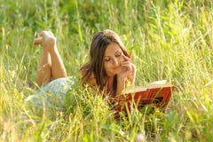 Femme se situant dans l'herbe Photographie stock
