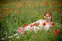 Femme se situant dans l'herbe parmi des pavots Images stock