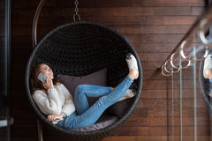 Femme se situant dans la chaise de bulle et parlant sur le téléphone portable Photographie stock