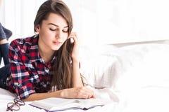 Femme se situant dans le lit avec le livre et sembler heureux à l'appareil-photo Photos libres de droits