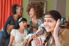 Femme se tapissante et amis chanteurs Photographie stock