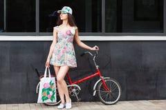 Femme se tenant à côté de la rétro bicyclette Image stock
