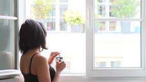 Femme se tenant à la fenêtre avec la tasse banque de vidéos