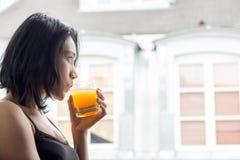 Femme se tenant à une fenêtre ouverte photographie stock libre de droits