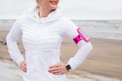 Femme se tenant avant exercice sur la plage en hiver Image libre de droits