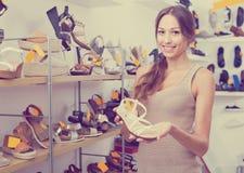 Femme se tenant avec la chaussure choisie Image stock