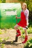 Femme se tenant avec la pelle dans le jardin image stock
