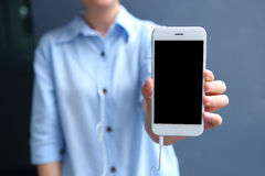 Femme se tenant avec montrer le smartphone de la vue de face OD avec du Ba bleu Photographie stock