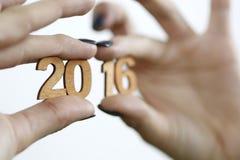 Femme se tenant dans des nombres en bois d'une année 2016 de main nouvelle Photo libre de droits