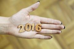Femme se tenant dans des nombres en bois d'une année 2016 de main nouvelle Photo stock
