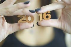 Femme se tenant dans deux nombres en bois de la nouvelle année 2016 de mains Photographie stock libre de droits