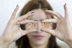 Femme se tenant dans deux nombres en bois de la nouvelle année 2016 de mains Photo stock