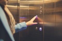 Femme se tenant dans l'ascenseur et appuyant sur le bouton image stock
