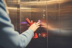 Femme se tenant dans l'ascenseur et appuyant sur le bouton photo stock