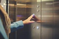 Femme se tenant dans l'ascenseur et appuyant sur le bouton images stock