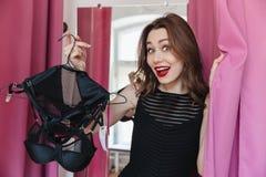 Femme se tenant dans la boutique de vêtements tenant à l'intérieur la lingerie Photographie stock