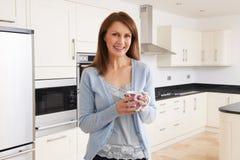 Femme se tenant dans la cuisine adaptée nouveau par luxe photo stock