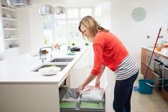 Femme se tenant dans la cuisine vidant la poubelle de rebut Image stock
