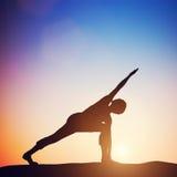Femme se tenant dans la pose tournée de yoga d'angle latéral méditant au coucher du soleil Images libres de droits