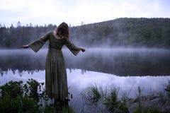 Femme se tenant dans la robe au lac Images stock