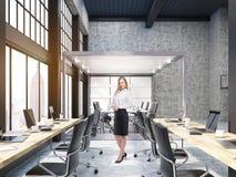 Femme se tenant dans le bureau ouvert avec la salle du conseil d'administration en verre à New York Photos stock