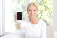 Femme se tenant dans son téléphone portable de main Images stock