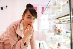 Femme se tenant devant l'étalage en verre avec des pâtisseries à l'intérieur Image libre de droits