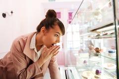 Femme se tenant devant l'étalage en verre avec des pâtisseries à l'intérieur Images stock