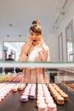 Femme se tenant devant l'étalage en verre avec des pâtisseries Photo stock