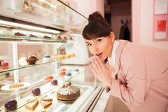 Femme se tenant devant l'étalage en verre avec des pâtisseries Photographie stock libre de droits