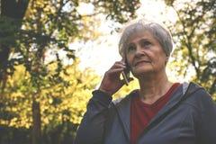 Femme se tenant en parc et parlant au téléphone intelligent photos libres de droits