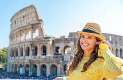 Femme se tenant près de Colosseum à Rome ajustant l'earbud Photographie stock libre de droits