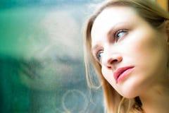 Femme se tenant prêt une fenêtre regardant dehors image stock