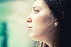 Femme se tenant prêt une fenêtre regardant dehors Image libre de droits