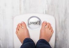 Femme se tenant sur l'échelle de poids montrant le message d'erreur photographie stock