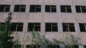 Femme se tenant sur la fenêtre du bâtiment à plusiers étages détruit avec beaucoup de fenêtres cassées banque de vidéos