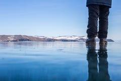 Femme se tenant sur la glace bleue du lac Baïkal congelé avec la réflexion Photographie stock