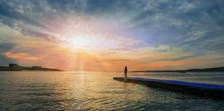 Femme se tenant sur la jetée près de la mer au coucher du soleil Photographie stock libre de droits