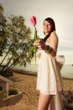 Femme se tenant sur la plage donnant la tulipe rose Photos stock